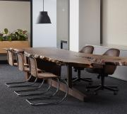 Live edge conference table with walnut slab top and custom cantilever base, under mount technology access